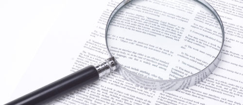magnifying glass on legal documents