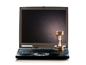 Old, outdated laptop with an hourglass sitting on it